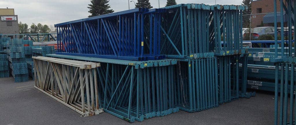 Used pallet racking frames/uprights stacked outside