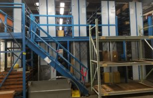 Equipto shelving-supported mezzanine in use inside of warehouse. Front view with staircase.