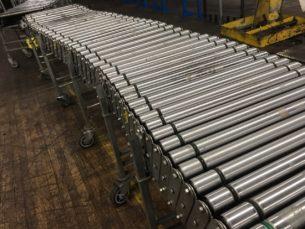 Used NestaFlex power roller conveyor in warehouse