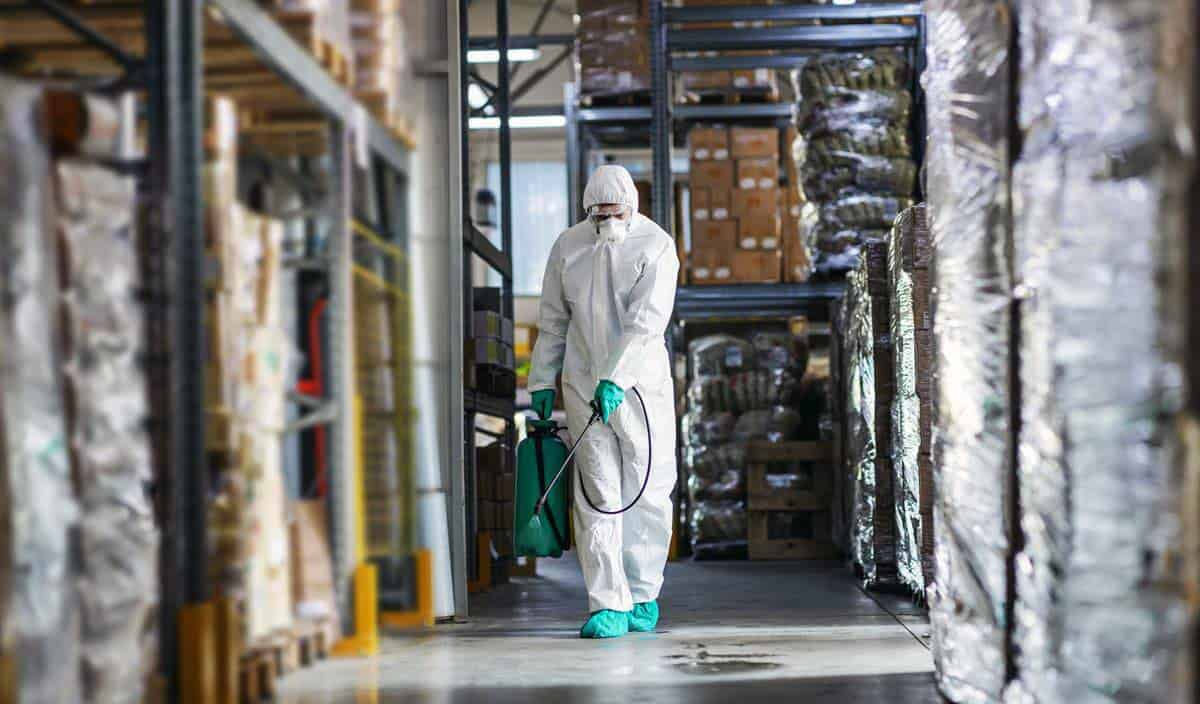 Man spraying disinfectant in warehouse
